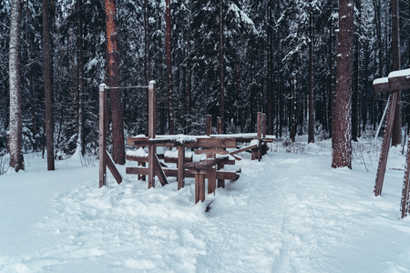 Empty gym in the forest mildly covered with some snow on a winter day
