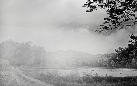 Black and white country lane by lake