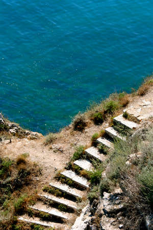 stoned: Stoned stairs leading to the sparkling blue sea. A  summer scenery Stock Photo