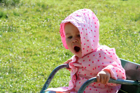 Baby sitting on the chair (carousel) in the garden and yawning Stock Photo