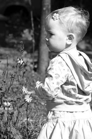 Little girl walking in the forest looking at the flowers