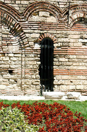 An ancient wall with the entrance with the grating and little flowerbed ahead Stock Photo