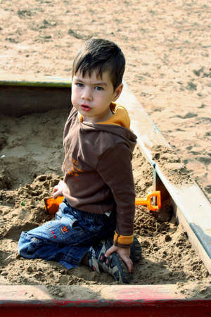 Little boy playing in the sand-box outside Stock Photo