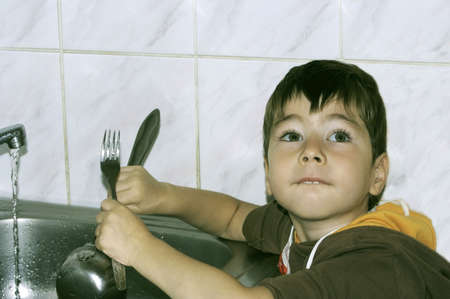 Little boy helping his parents to wash up the dishes on the kitchen