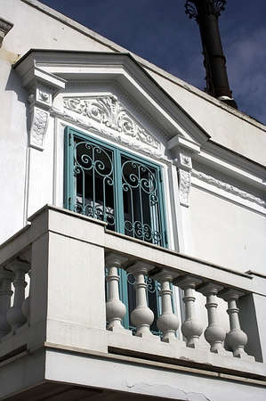 classical balcony of the white house with blue shutters Stock Photo
