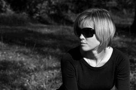 Pretty young woman in sunglasses dreaming sitting in the park