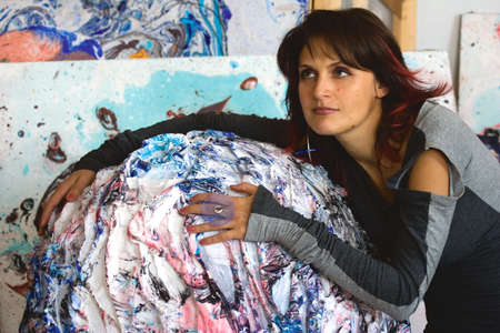Popular painter in her studio with her works and sketches