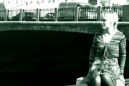 Girl in stress sitting near the bridge of the city Stock Photo