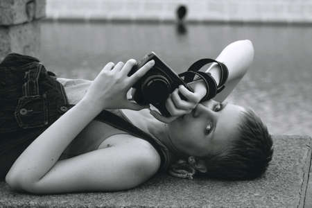 Young sexy woman with the camera lying near the river
