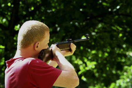 Young man with a hunting rifle shooting straight