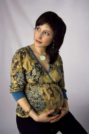 Nice pregnant with a tender smile in a motley jacket