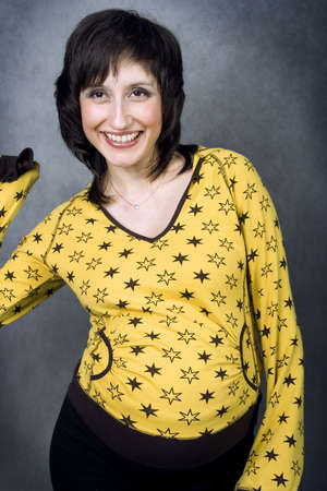 Energetic laughing expecting mother in a yellow pijamas with stars