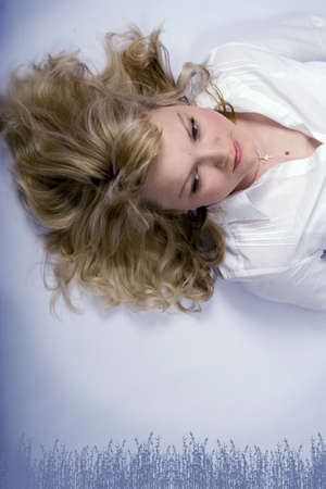 Pretty dreaming blonde woman with curly hair on the blue background