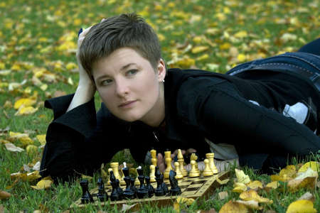 Charming woman lying with the chess board on the grass