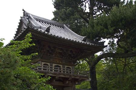 Oriental house in japanese garden through the trees