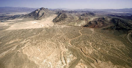 Lifeless dry desert with several picks in a hot weather Stock Photo