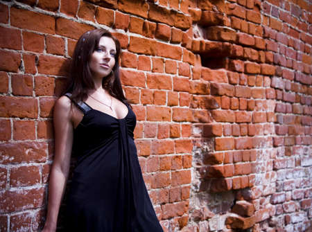 Charming young woman in black dress near the brick wall