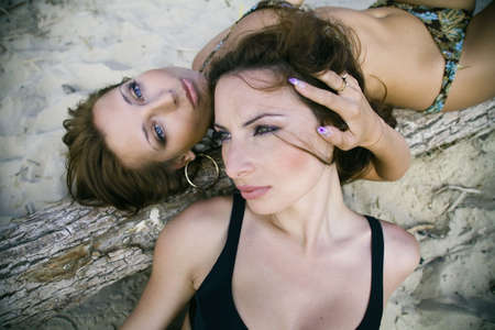 Two sensual girls lying closely on the beach Stock Photo