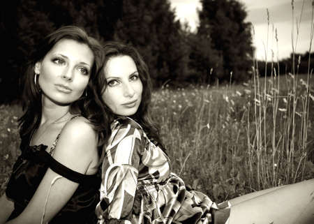 Two sensual girls sitting closely in the grass Stock Photo