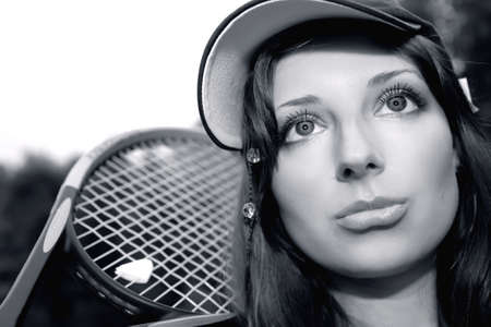 Pretty tennis player with racket in monochrome