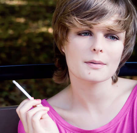 Attractive young woman in pink smoking cigarette