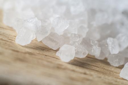 sal: Macro close-up de sal marina gruesa derramó sobre tabla de madera