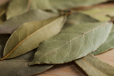 dry provisions: Dry bay leaves spilled on wooden board