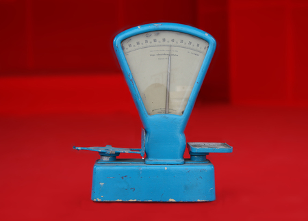 communism: Old worn blue weighing scale on red background, souvenir of the communism era in Poland