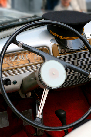 communism: Dashboard of old car with steering wheel and cap of driver, souvenir of the communism era