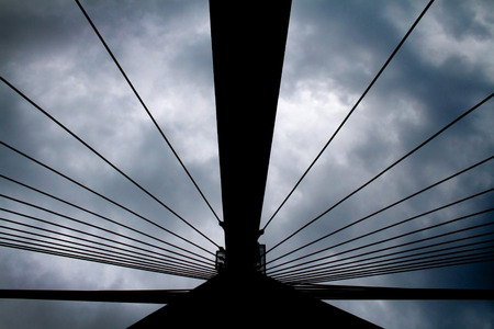 sightsee: Pylon of Swietokrzyski bridge over Vistula in Warsaw seen from bottom against cloudy sky making abstract pattern Stock Photo
