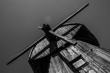 Lublin, Poland, august 2018, Old wooden windmill against sky in Open Air Village Museum, monochrome