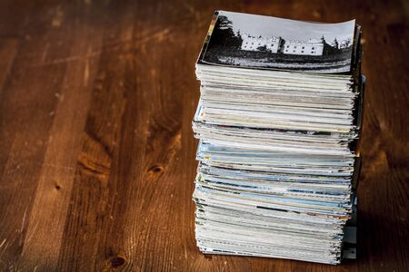 Stack of few hundrets old postcards collection on table