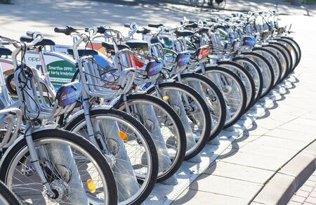 Warsaw, Poland: City bicycles parked in a row on bicycle parking - seen plaques with advertisements