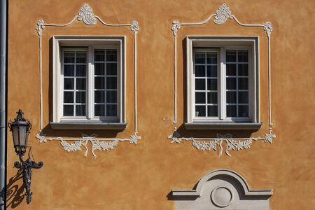 Windows with decorations and lanter on the wall of renovated old tenement house in Gdansk Old Town, Poland