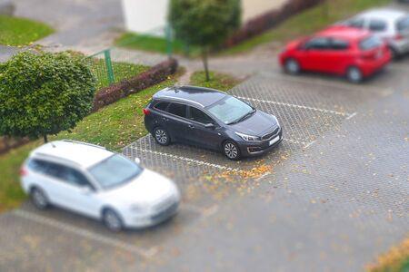 Aparcamiento pequeño con diferentes coches vistos desde arriba con efecto de cambio de inclinación Foto de archivo