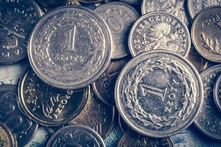 Due monete da uno zloty su altre monete e banconote polacche