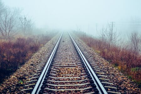 Perspective of railway track disappearing in mist in foggy morning