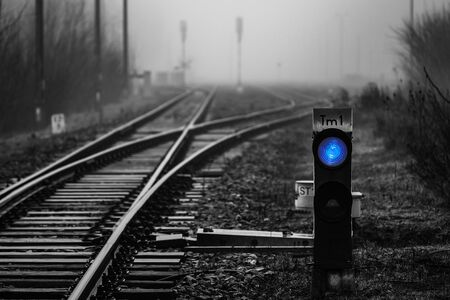 Railway signal with blue light with railroad junction disappearing in mist, monochrome image with blue colour
