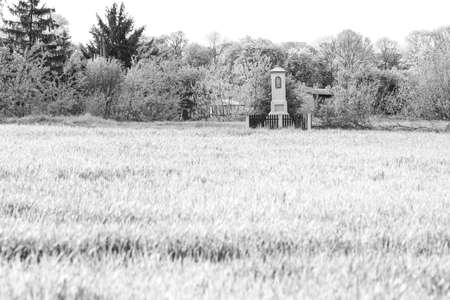 Old wayside shrine in polish countryside stand amid fields of rye, infrared black and white image