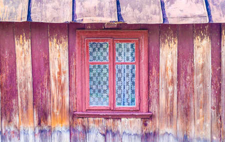 Window in brown painted frame of very old wooden house