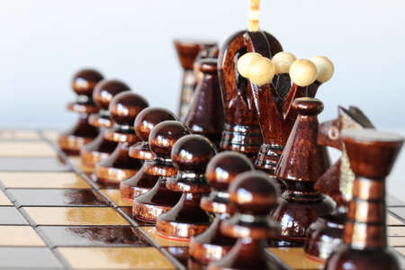 White chess pieces arranged on chess board before start of gameplay as army before war