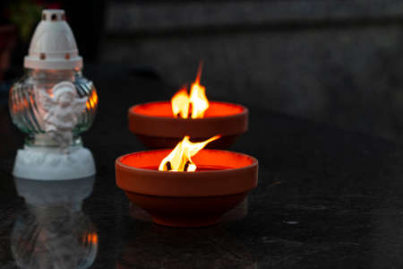 Traditional burning grave candles and decorative one on a black marble grave during All Souls' Day with copy space