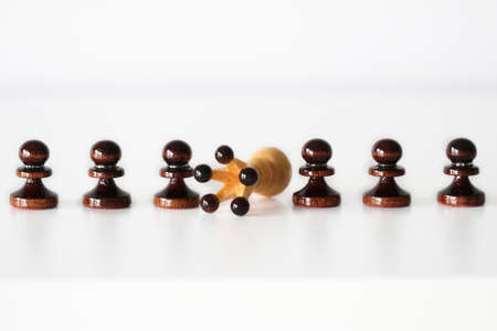 Row of black pawn chess pieces with knocked down white queen in the middle on white background - strength in numbers concept