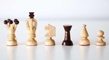 All six chess pieces in a row on white background, black rook amid white pieces as stand out of the crowd concept