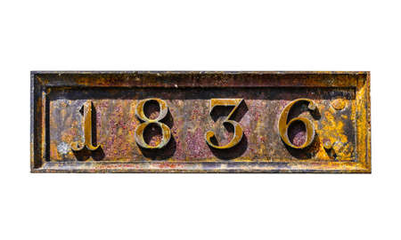 Rusty metal plate with 1836 date of built of old Napoleon fortress on white plaster