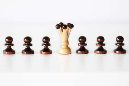 Row of black pawn chess pieces with white queen in the middle on white background - stand out of the crowd concept Stock Photo