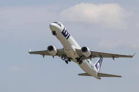 Polish airlines LOT Embraer 195 LR jetliner on the climbout after take-off from Warsaw Chopin Airport