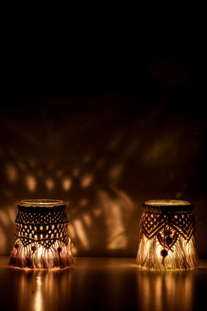 Macrame hand woven with cord two lanterns glow making abstract shadow patterns on the wall