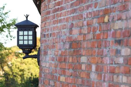 Old steel electric lantern attached to red brick wall