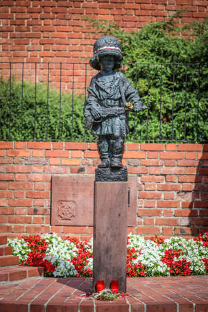 Monument of little boy insurgent in oversized german helmet and boots, participant of Warsaw Uprising in 1944 against red brick of medieval city walls